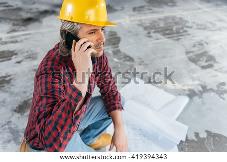 Construction Worker In Safety Helmet reading blueprints and talking on smart phone