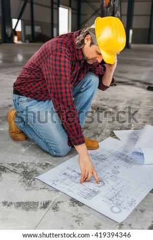 Construction worker safety helmet reading blueprints stock photo construction worker in safety helmet reading blueprints and talking on smart phone malvernweather Images