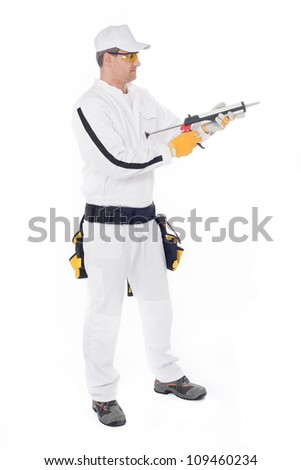 construction worker in white overalls holding a gun with silicon - stock photo