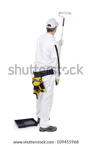 construction worker in white overalls with paint roller paint walls - stock photo