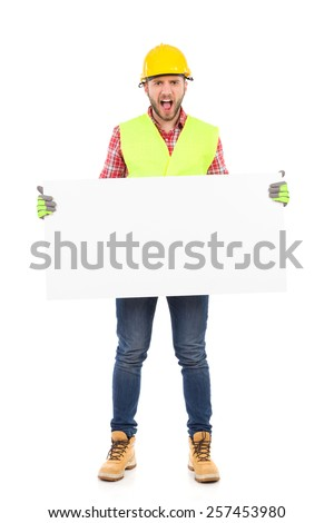 Construction worker in yellow helmet and reflective waistcoat holding white placard and shouting. Full length studio shot isolated on white. - stock photo