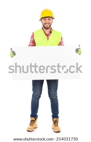 Construction worker in yellow helmet and reflective waistcoat holding white placard. Full length studio shot isolated on white. - stock photo
