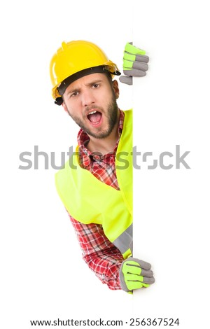 Construction worker in yellow helmet and reflective waistcoat peeking behind big white banner and shouting. Studio portrait isolated on white. - stock photo