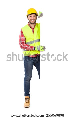 Construction worker in yellow helmet and reflective waistcoat standing behind big white banner. Full length studio shot isolated on white. - stock photo
