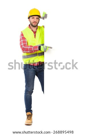 Construction worker in yellow helmet and reflective waistcoat standing behind big white banner and pointing. Full length studio shot isolated on white. - stock photo