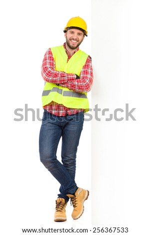Construction worker in yellow helmet and reflective waistcoat standing leaning on a big white banner. Full length studio shot isolated on white.