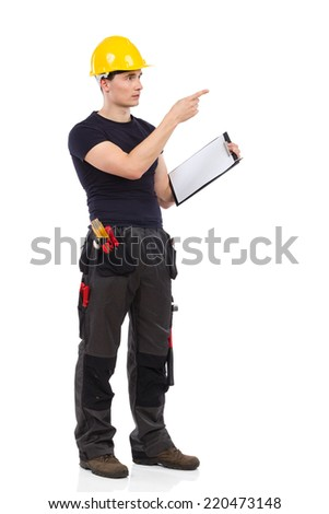 Construction worker in yellow helmet holding clipboard and directing.  Full length studio shot isolated on white.