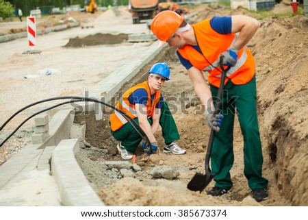Construction worker installing electrical cables at construction site - stock photo