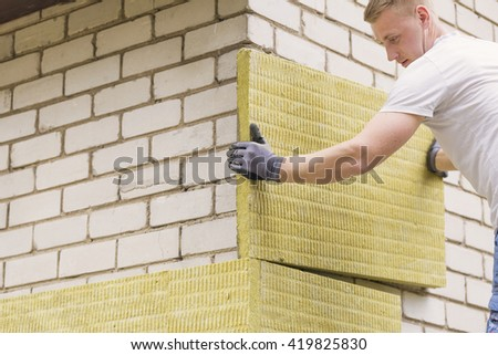 construction worker insulating house facade with mineral rock wool - stock photo