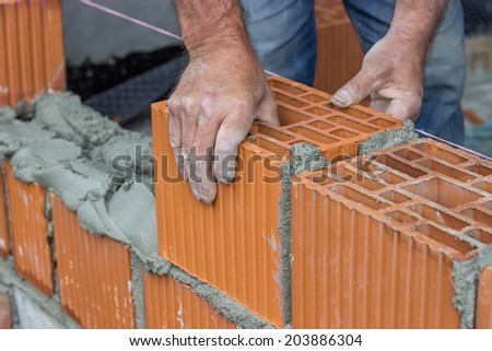 Construction worker laying hollow clay block at construction site - stock photo