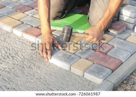 construction worker laying sidewalk tiles in the yard of the house