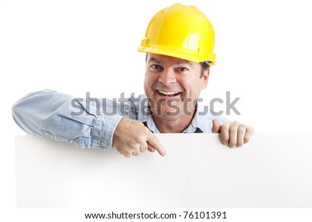 Construction worker leaning over and pointing to blank white space.  Isolated. - stock photo