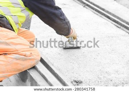 Construction worker leveling concrete pavement. - stock photo