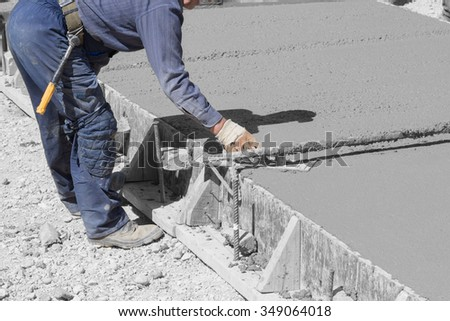 Construction worker leveling concrete pavement.