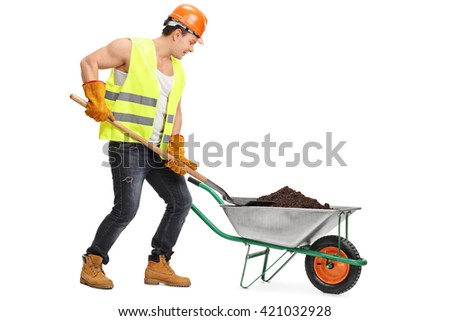Construction worker loading dirt into a wheelbarrow isolated on white background - stock photo