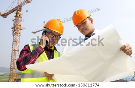 Construction worker looking at plans, conversation via mobile phone - stock photo