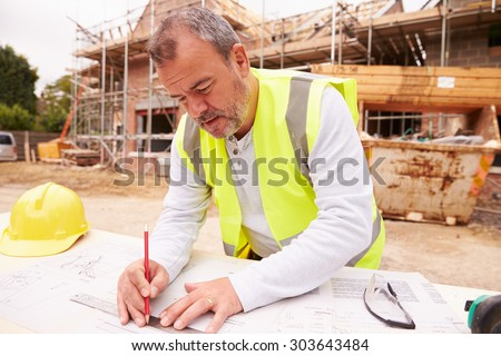 Construction Worker Looking At Plans On Building Site - stock photo