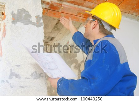 Construction worker looks at the ceiling - stock photo