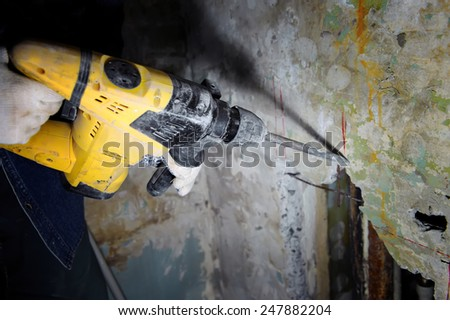 Construction worker making hole a using pneumatic hammer - stock photo