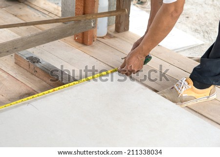construction worker man measuring plank of tile for Home Building - stock photo