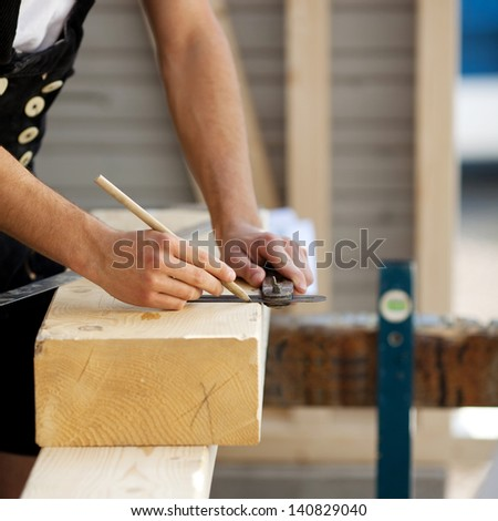 Construction worker marks a piece of wood - stock photo