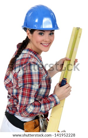 Construction worker measuring a piece of wood - stock photo