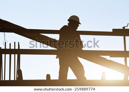 Construction worker on a high building with sunset flare. - stock photo