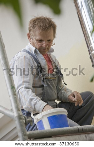 construction worker on a scaffold painting house - stock photo