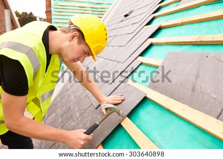Construction Worker On Building Site Laying Slate Tiles - stock photo