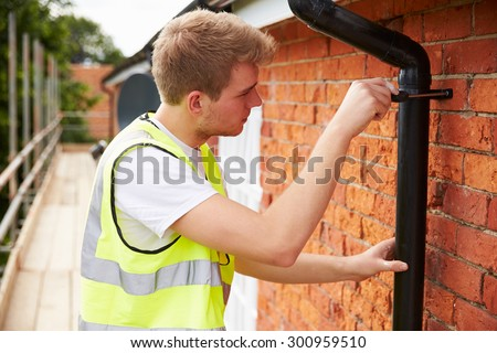 Construction Worker On Scaffolding Fixing Drain Pipe - stock photo