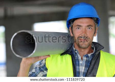 Construction worker on site holding pipe - stock photo