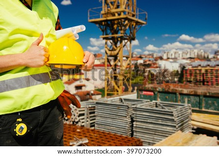 Construction worker on site, thumbs up. Construction material, tower crane and city in the background - stock photo