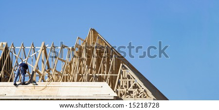 Construction worker on the roof building a house