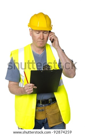 Construction worker on white background looks at clipboard and takes phone call - stock photo