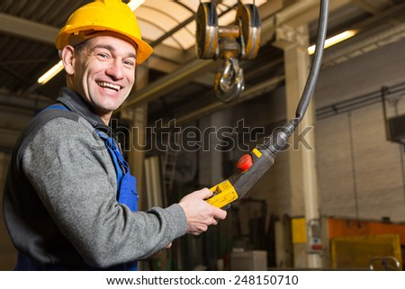 Construction worker operating a crane in assembly hall - stock photo