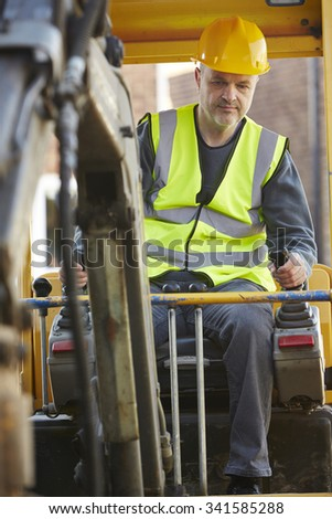 Construction Worker Operating Digger On Site