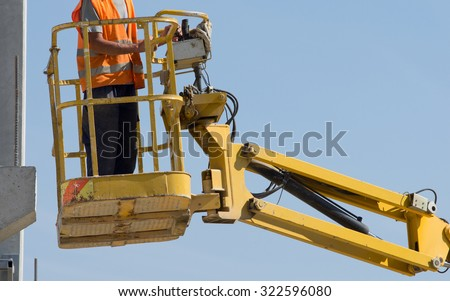 Construction worker operating with lifting security cage for works on height - stock photo