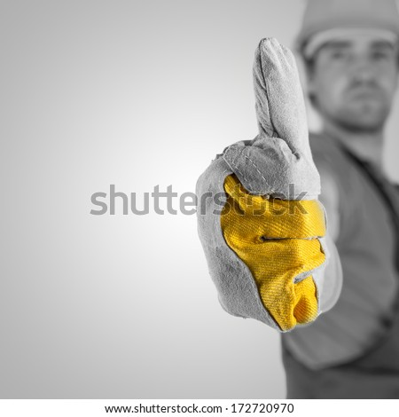 Construction worker or builder in a protective hardhat and gloves giving a thumbs up gesture of approval and success with selective focus to his gloved hand , greyscale image with yellow and copyspace - stock photo
