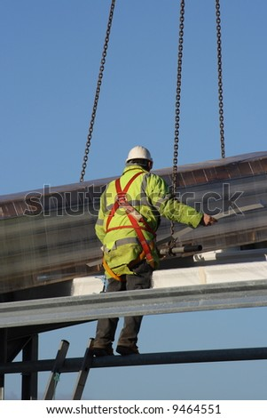 Construction worker perched on a metal structure.   - stock photo