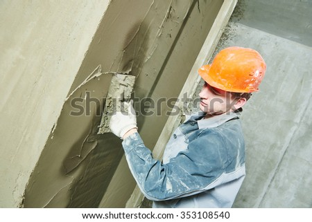 Construction worker plasterer with trowel plastering a wall - stock photo