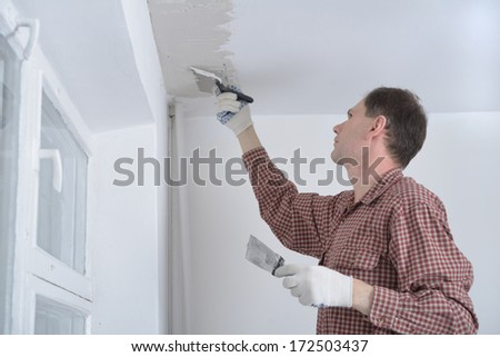 Construction worker plastering a ceiling