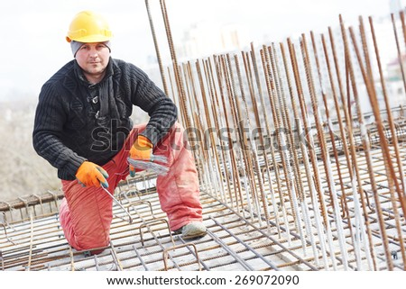 construction worker portrait during reinforcement work with metal rebar rods at building site - stock photo