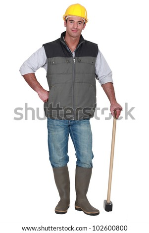Construction worker posing with sledge-hammer - stock photo