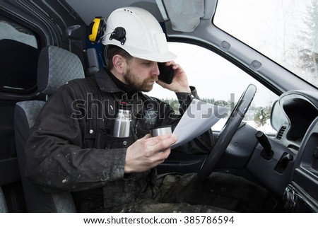 Construction worker reading papers, driving a car and talking on the phone while drinking coffee in Finland. He is wearing a white helmet and he has a dirty overalls. - stock photo