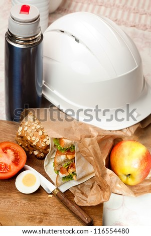 Construction worker's helmet and sandwich lunch bag
