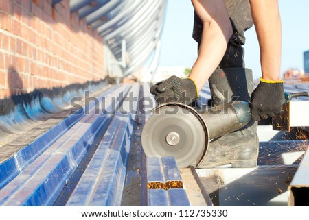 Construction worker sawing steel sheet with trapezoidal profile during roofing works - stock photo