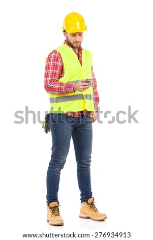 Construction Worker Sending a Text Message. Manual worker in yellow helmet and lime waistcoat using a smart phone. Full length studio shot isolated on white.