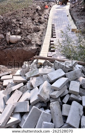 Construction worker setting paver bricks on footpath  - stock photo