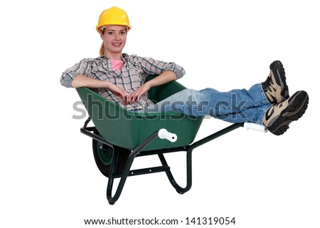 Construction worker sitting in a wheelbarrow - stock photo