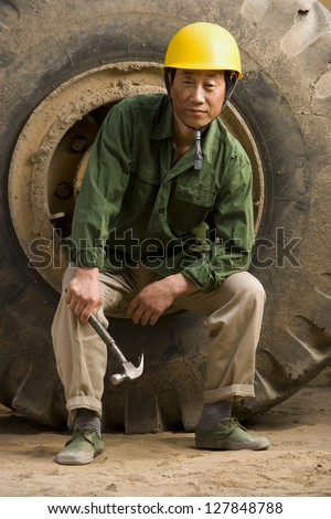Construction worker sitting on tire of large machine